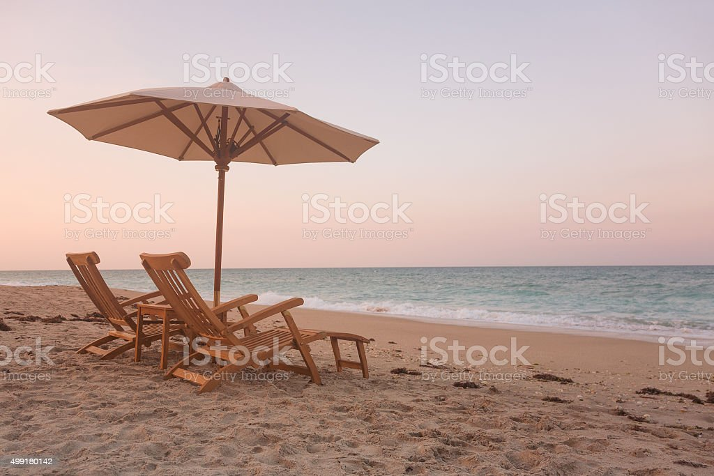 recliners and umbrella on a beach in Florida during sunset stock photo
