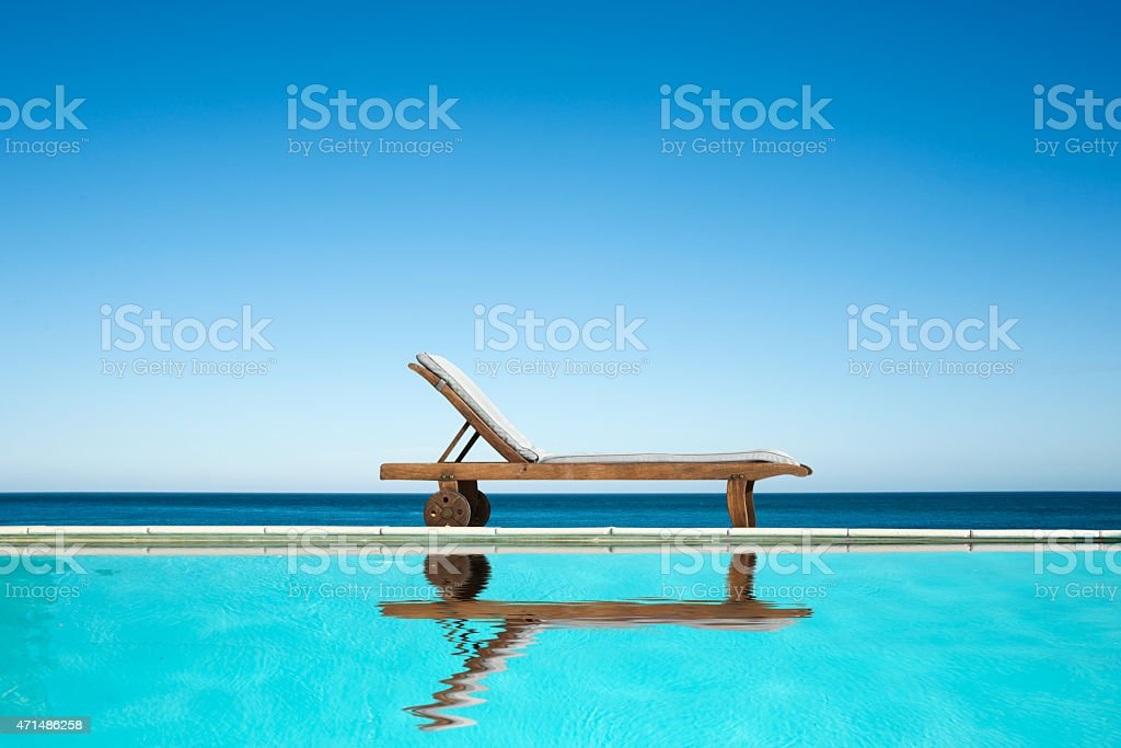 Reclining chair near a swimming pool, sea background stock photo