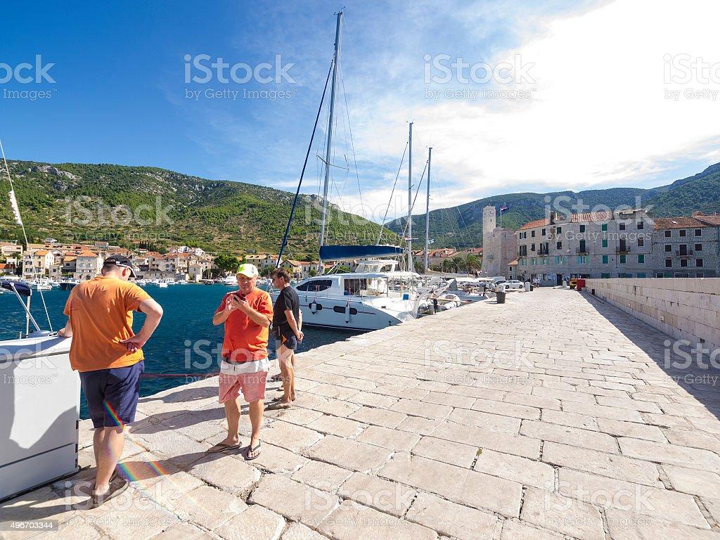 Recreational sailors with mobile phones on the Komiza pear, Croatia stock photo