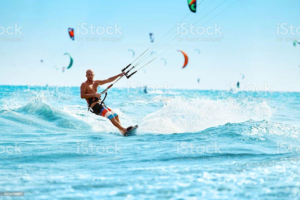 Recreational Sports. Healthy Man Kiteboarding On Waves In Sea Water....