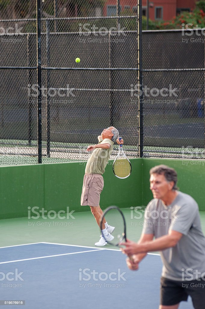 Recreational tennis doubles on serve stock photo