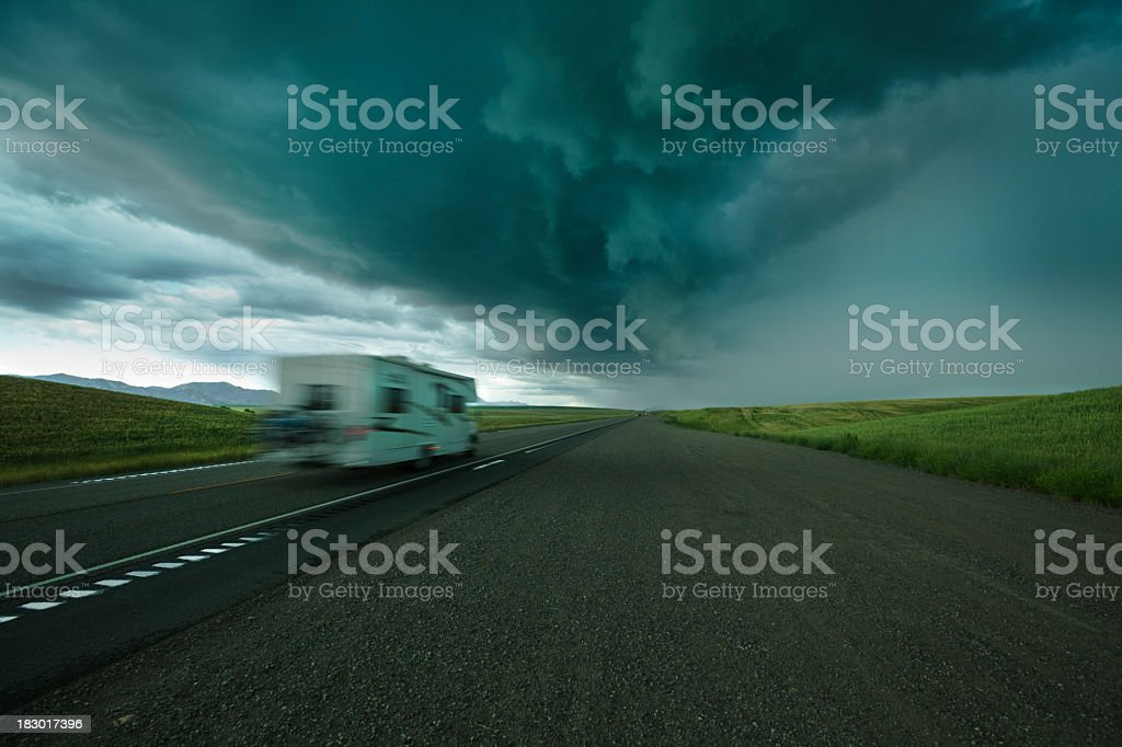 Recreational Vehicle Camper Driving on Highway Under Dark Storm Clouds royalty-free stock photo