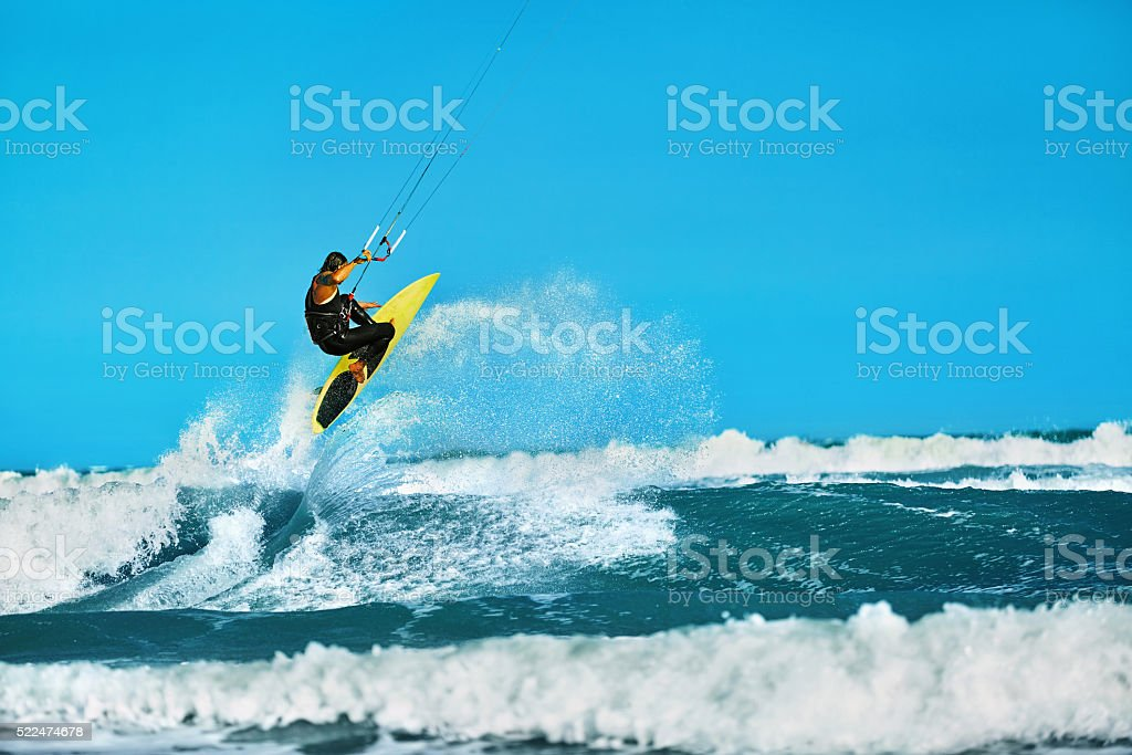 Recreational Water Sports Action. Healthy Man Kiteboarding On Waves...