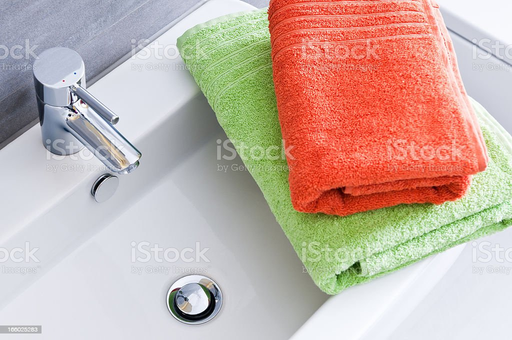 Rectangular bathroom sink with one green and one orange towel royalty-free stock photo