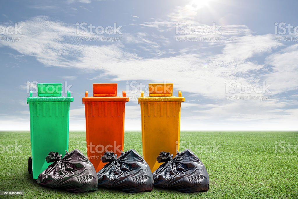 recycle bins and bag garbage on green grass and sky stock photo