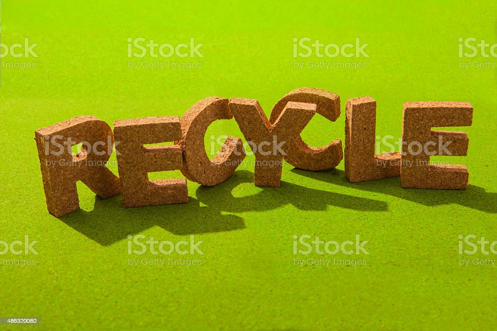 Recycle spelled out in letters on a green background stock photo