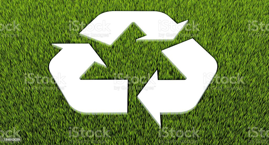 Recycle symbol cut into grass stock photo