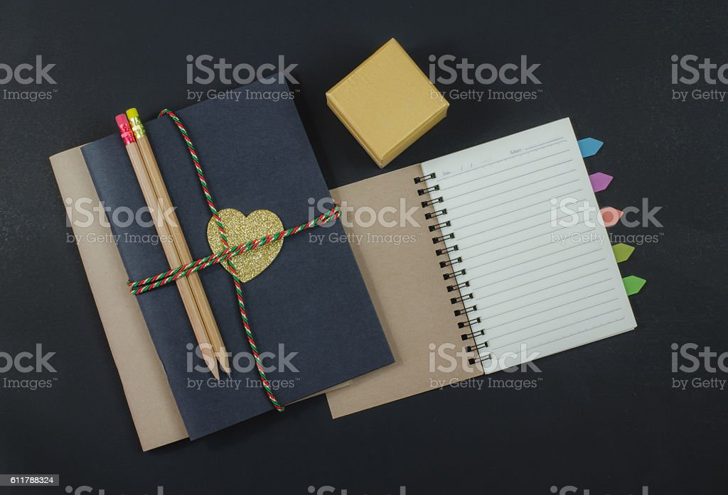 Recycled paper notebook pencils on black background