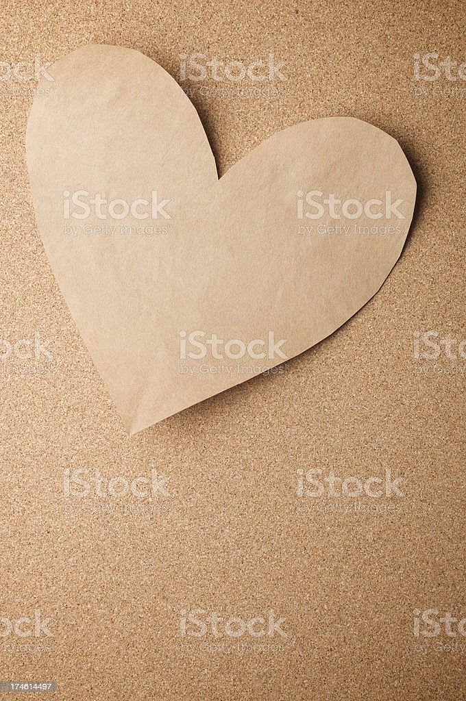 Recycled Plain Brown Paper Heart on Natural Cork Board royalty-free stock photo