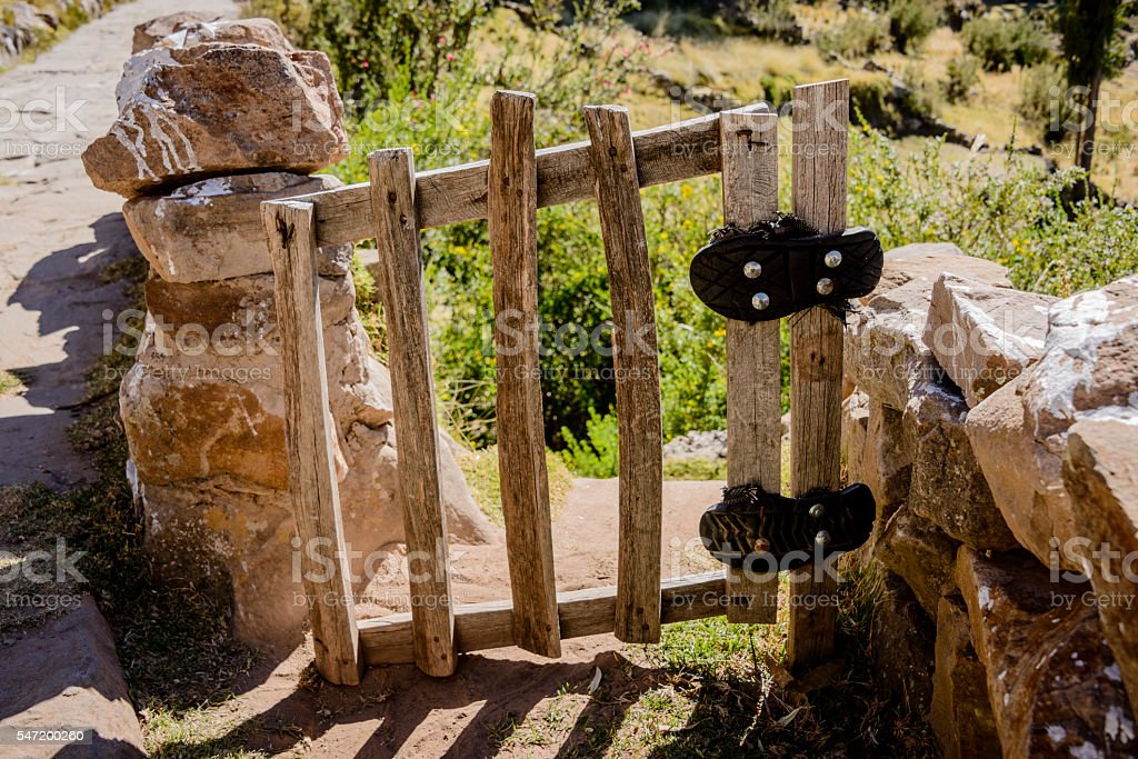 Recycled sandal soles used as gate hinge stock photo