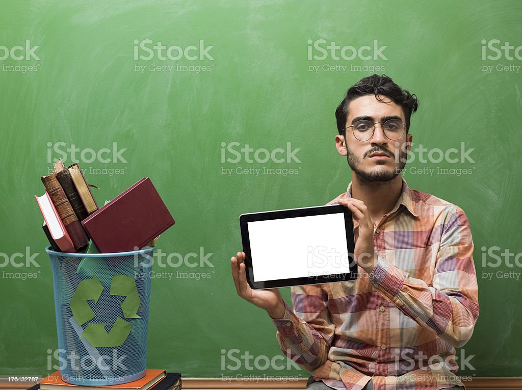 Recycling bin full of books and man holding tablet pc royalty-free stock photo