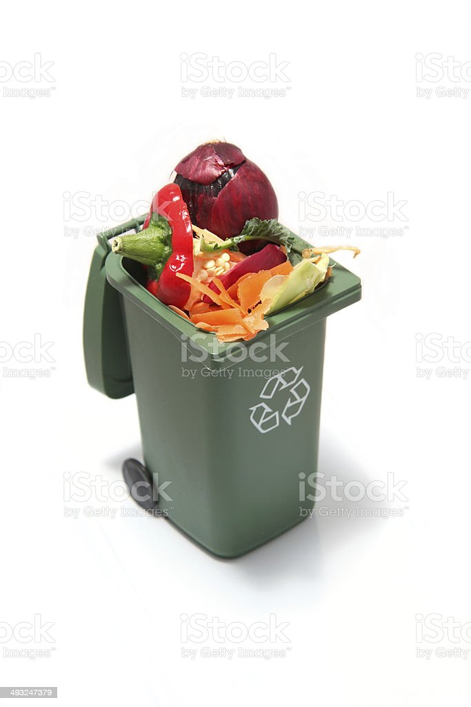 Recycling bin with vegetable scraps inside to turn to composte. stock photo