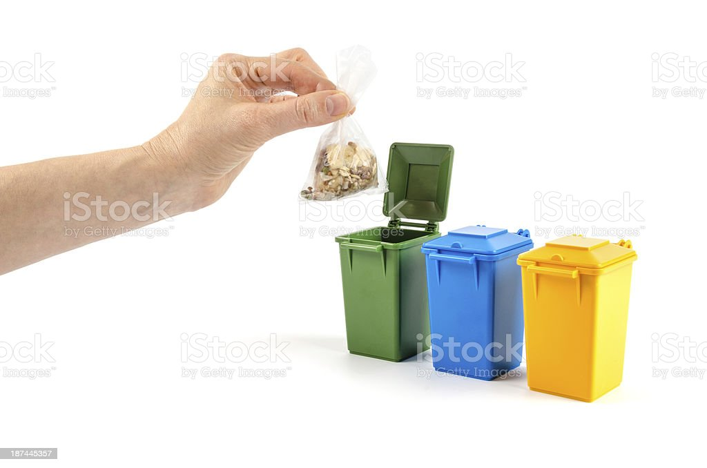 Recycling - Hand putting waste in a trash can stock photo