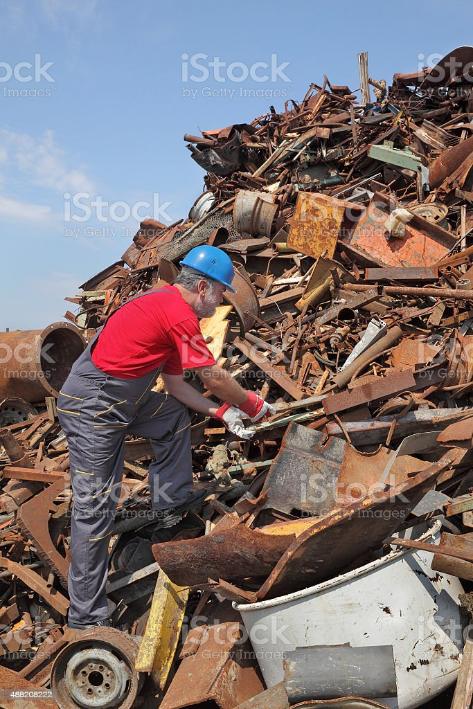 Recycling industry, worker at heap of old metal stock photo
