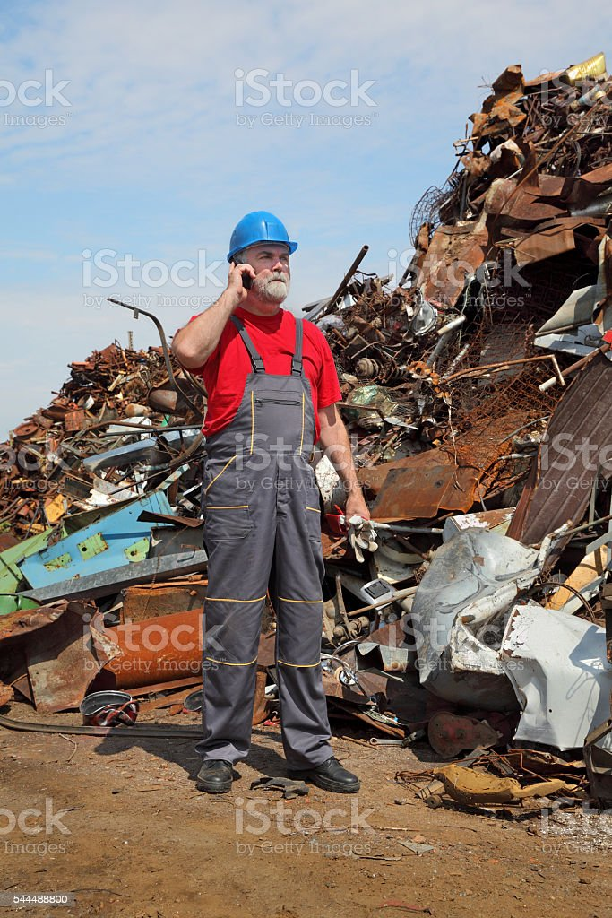 Recycling industry, worker using phone and heap of old metal stock photo