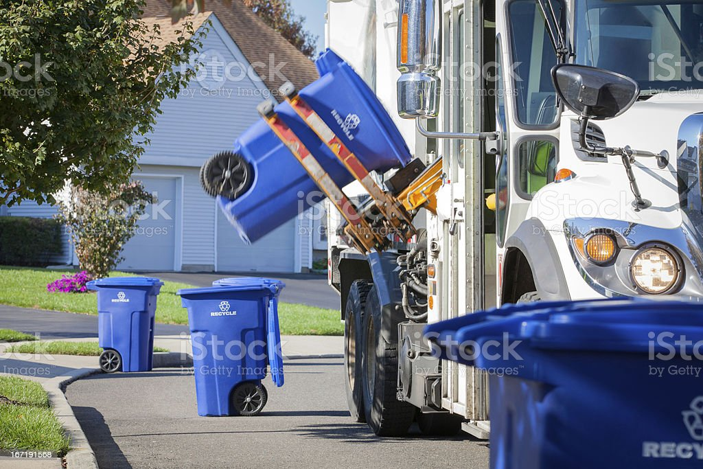 Recycling Truck Lifting Up Container Along Neighborhood Curb stock photo