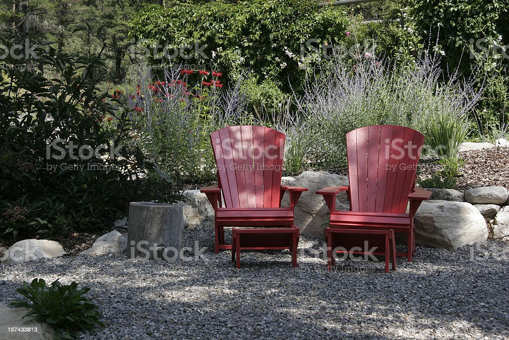 Red Adirondack Chairs And Blue Russian Sage In The Garden stock photo