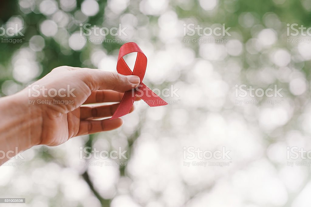 red aids ribbon in hand. stock photo
