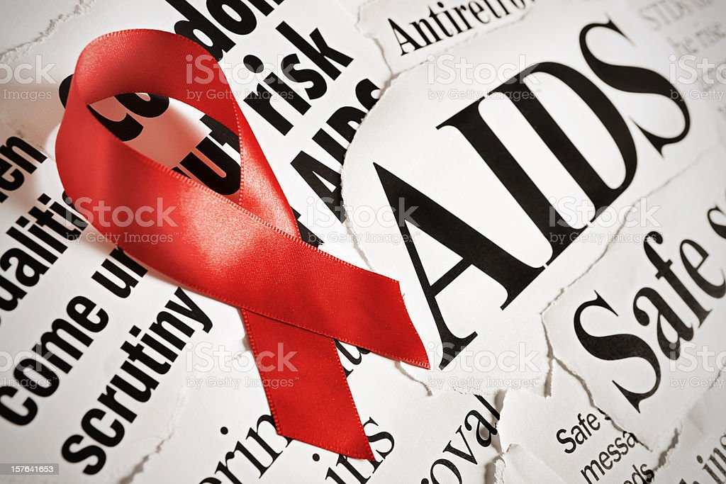 Red AIDS ribbon on headlines about aspects of the disease stock photo