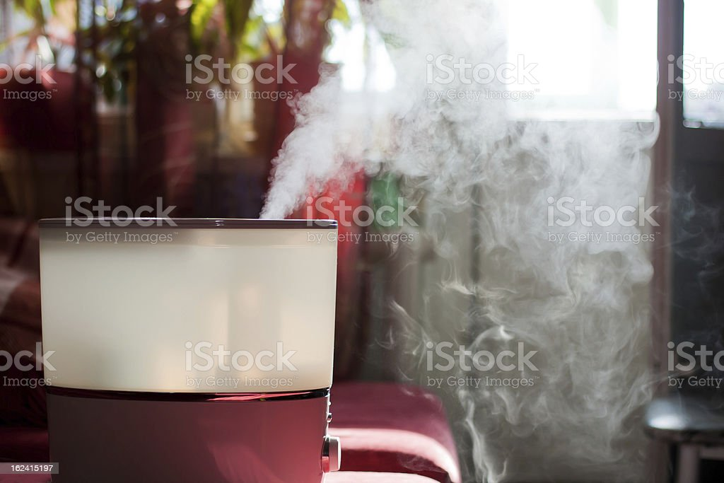 Red air humidifier emitting steam into room stock photo