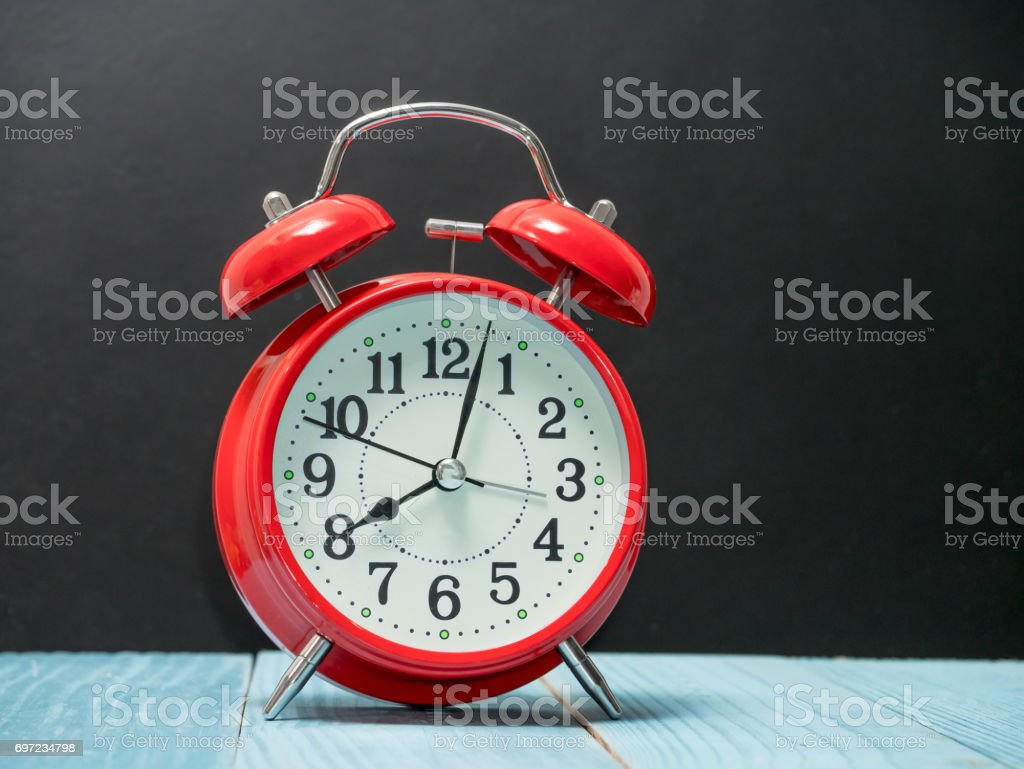 Red alarm clock on wood table stock photo
