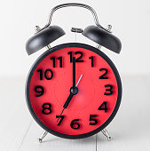 Red Alarm Clock on wooden tablet setting up at 7