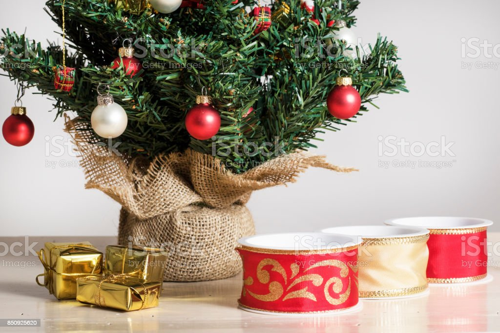 Red and beige silk ribbons golden wrapped parcels and details from a Decorated Christmas Tree stock photo