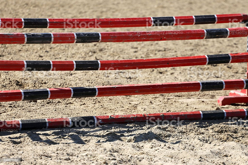 Red and black oxer on the ground for jumping horses stock photo