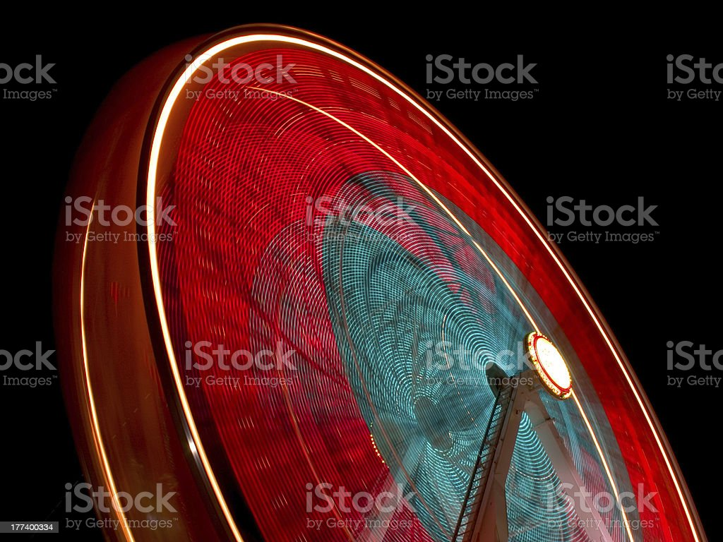 Red and blue Ferris wheel blurred at night stock photo