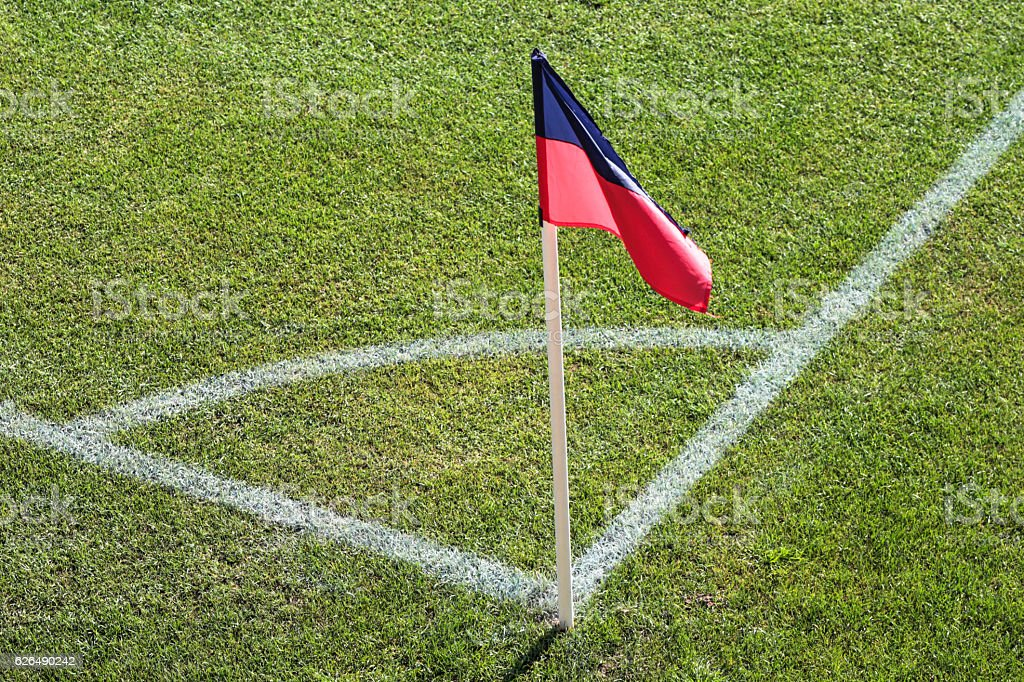 Red and blue flag at one corner of football stadium stock photo