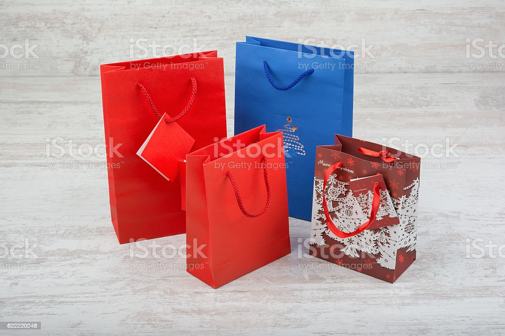 Red and blue gift bags on a white wooden background stock photo