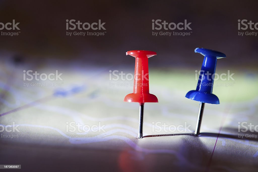 Red and blue push pins on a map royalty-free stock photo