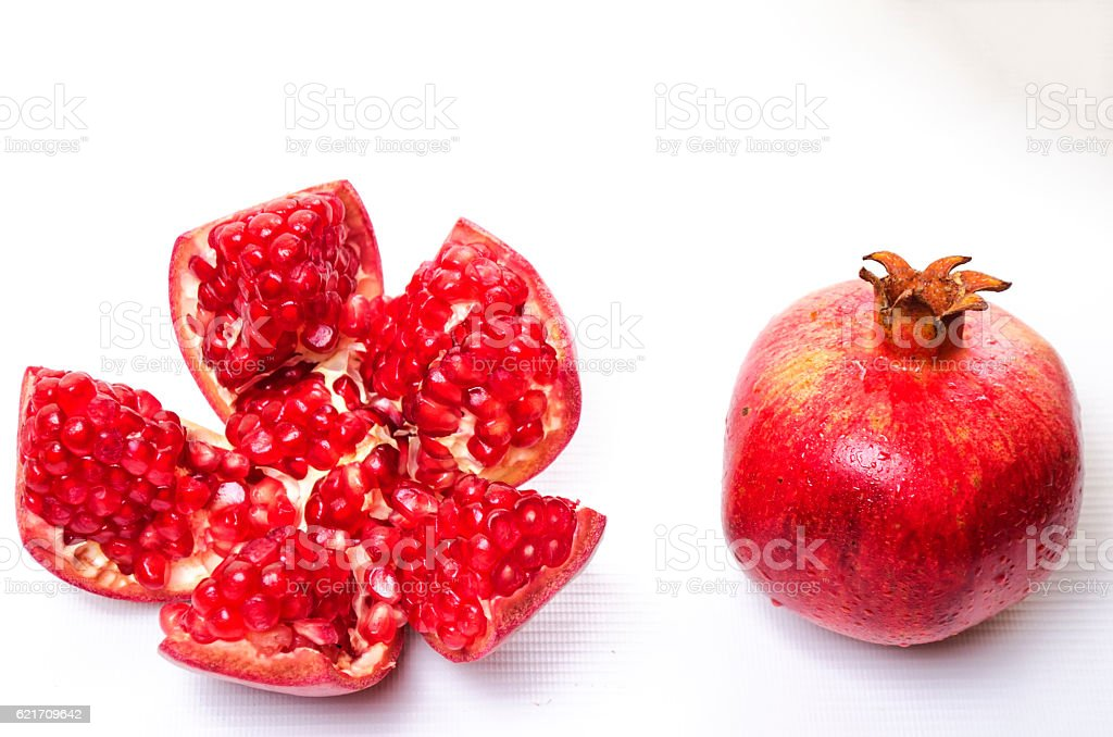red and fresh pomegranate on a white background stock photo