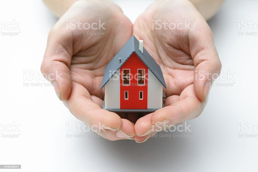 Red and gray model house in cupped hands on white background stock photo