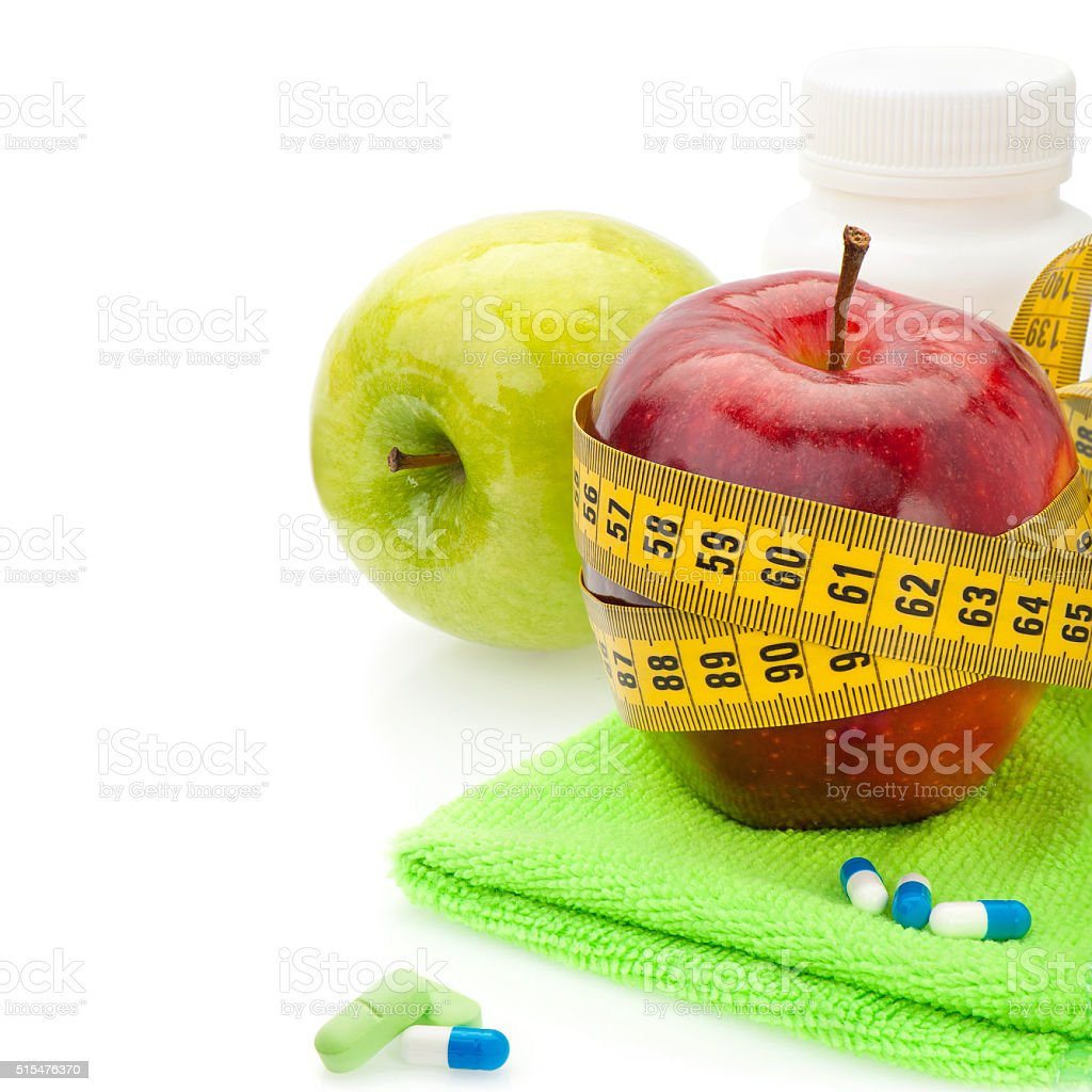 Red and green apples, vitamins and measuring tape stock photo