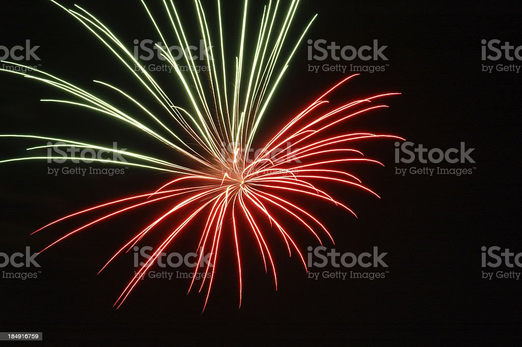 Red and green fireworks in dark sky stock photo