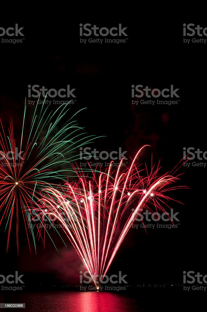 Red and green fireworks on the lake stock photo