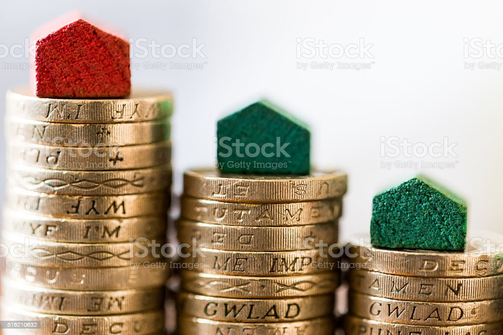 Red and Green Houses on top of Piles of Coins stock photo