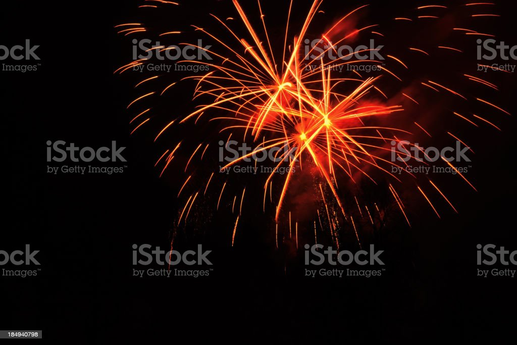 Red and orange fireworks sparks over a black background royalty-free stock photo