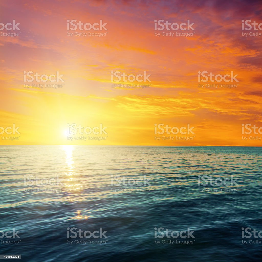 Red and orange sunset over dark sea stock photo