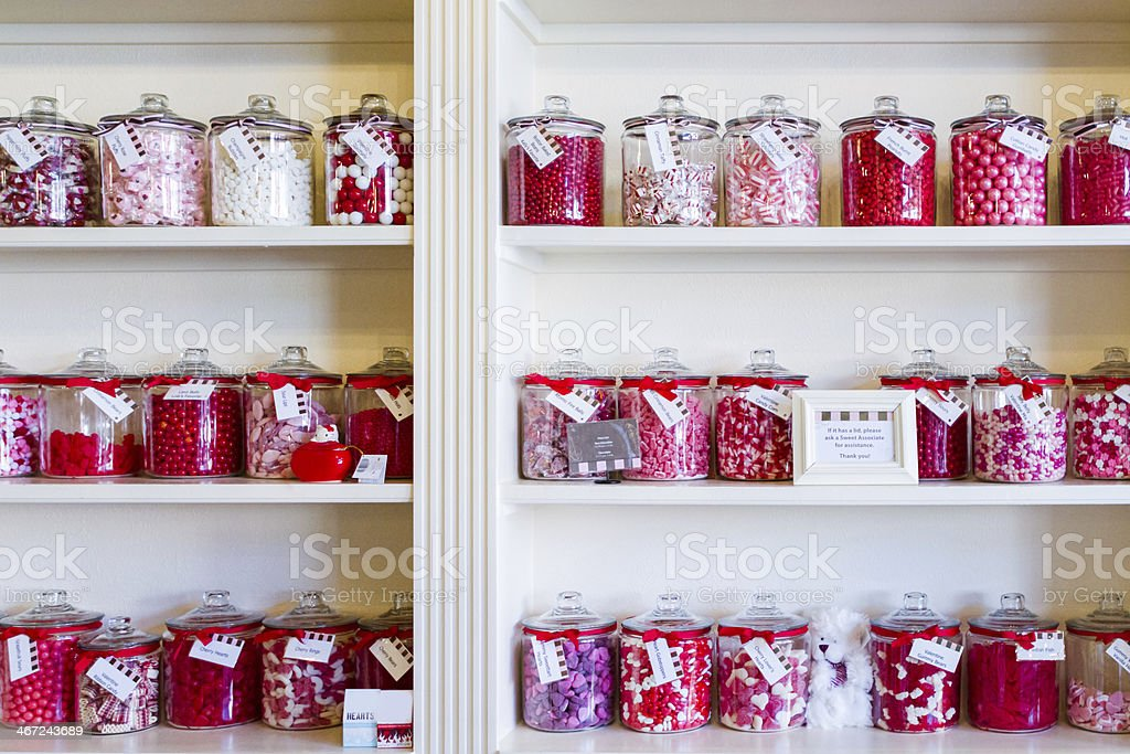 Red and pink sweets in jars in a candy store stock photo