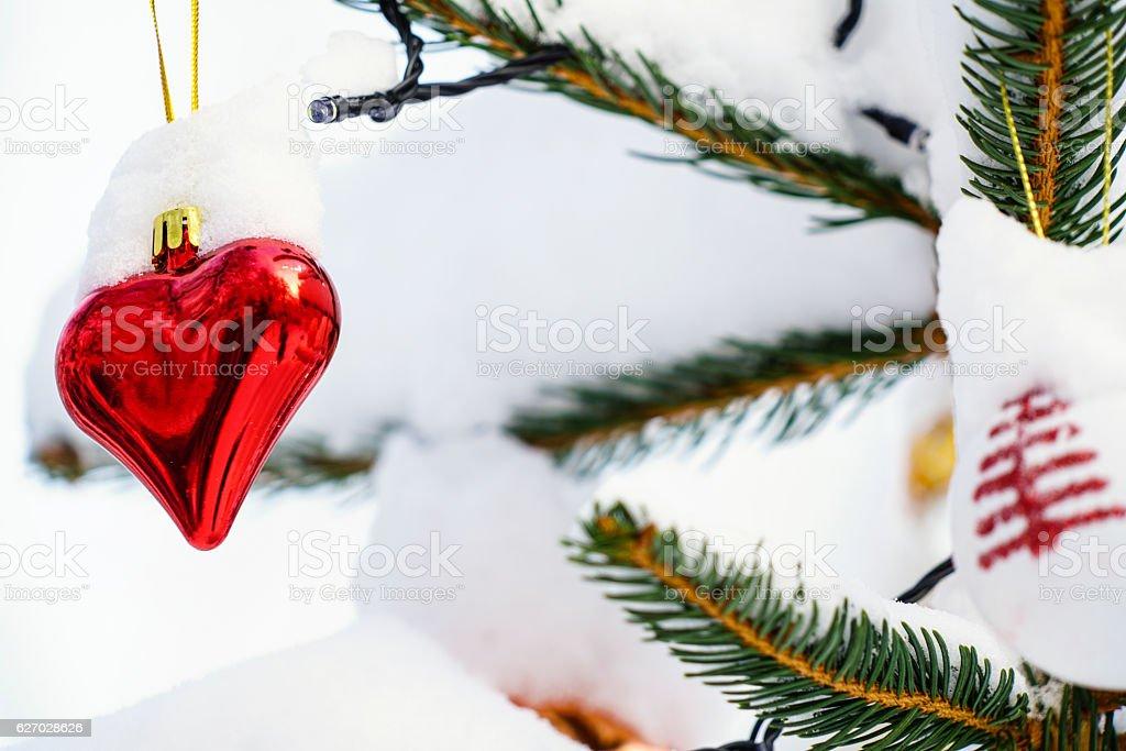 Red and Shining Christmas heart on Chrietmas tree stock photo