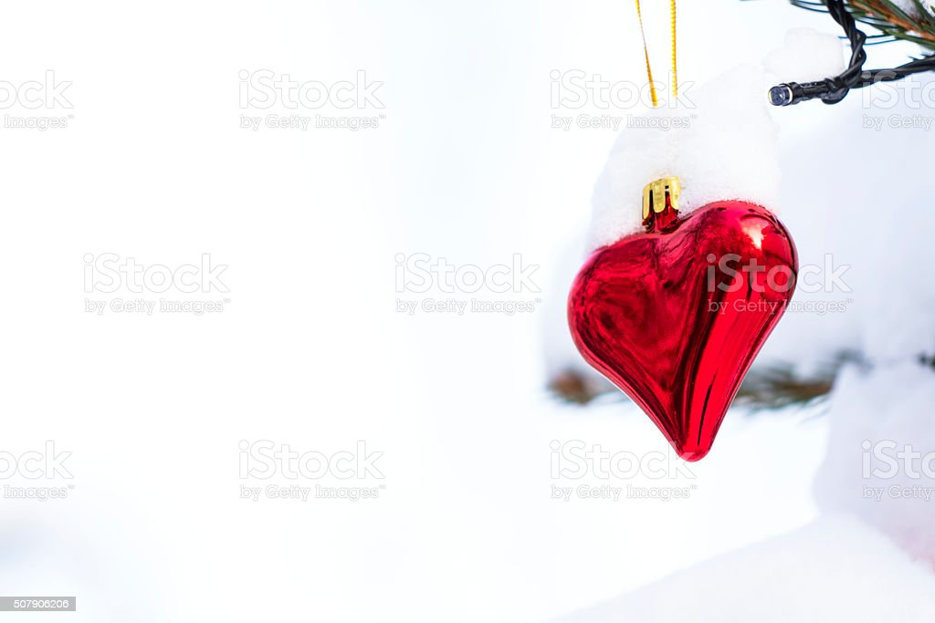 Red and Shining Valentine heart on snow background stock photo