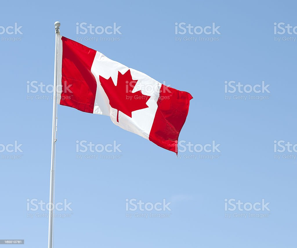 A red and white Canadian flag blows in the wind stock photo