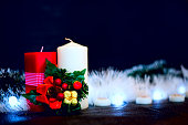 Red and white candles with garland at black background