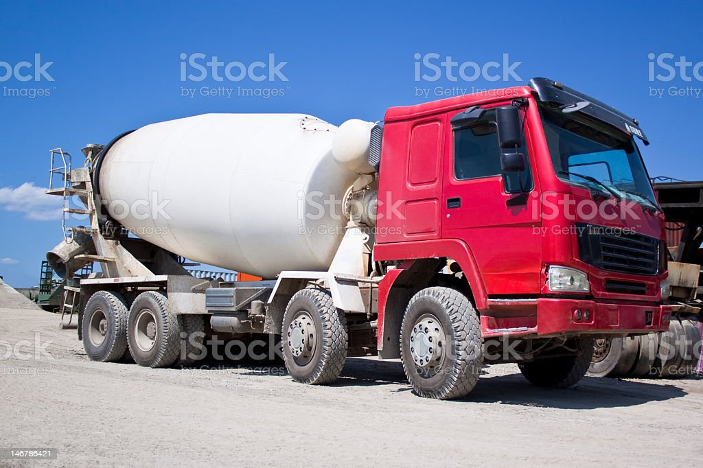 Red and white cement mixer on gravel road under blue sky stock photo