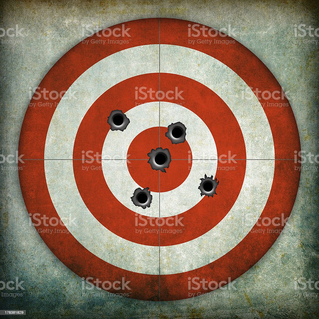 Red and white circular target with bullet holes stock photo