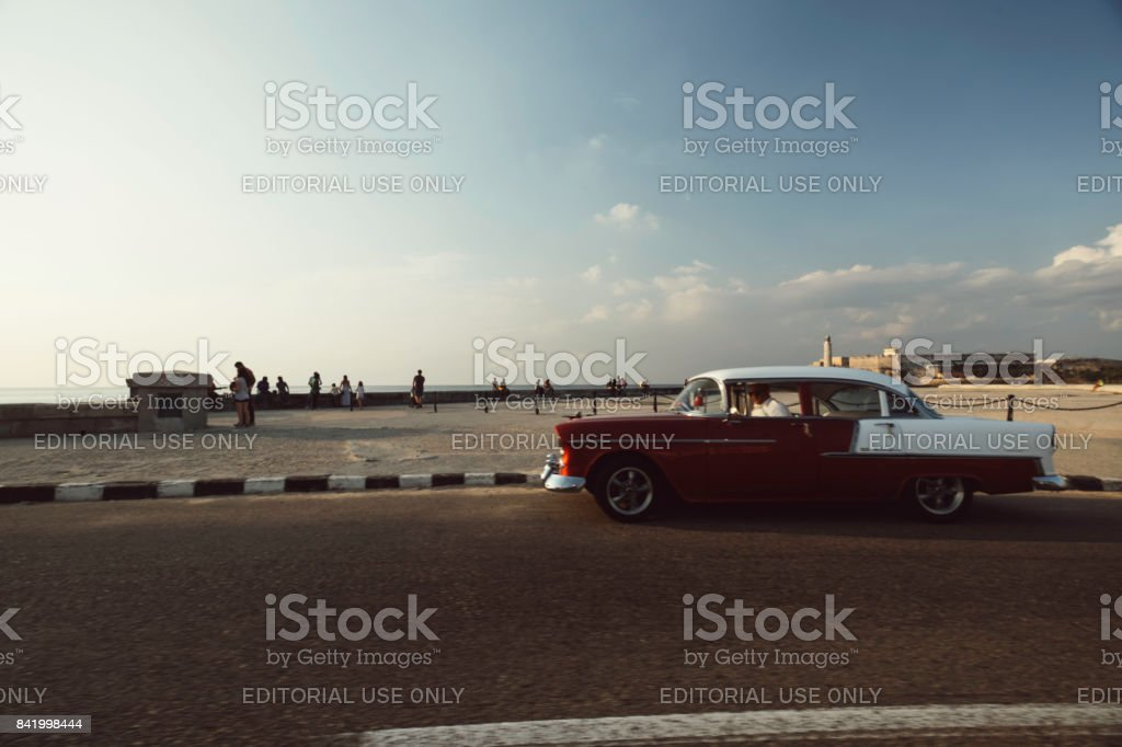 Red and white classic car on Malecon street at dusk in Havana stock photo