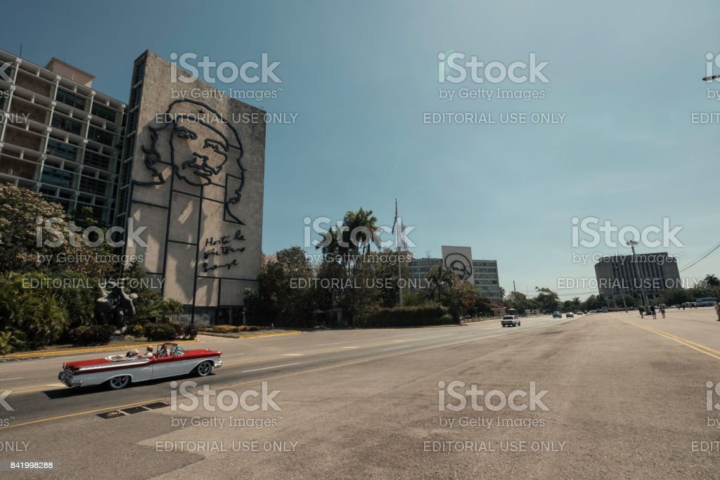 A red and white classic convertible taxi drives by the Che Guevara building in Havana stock photo