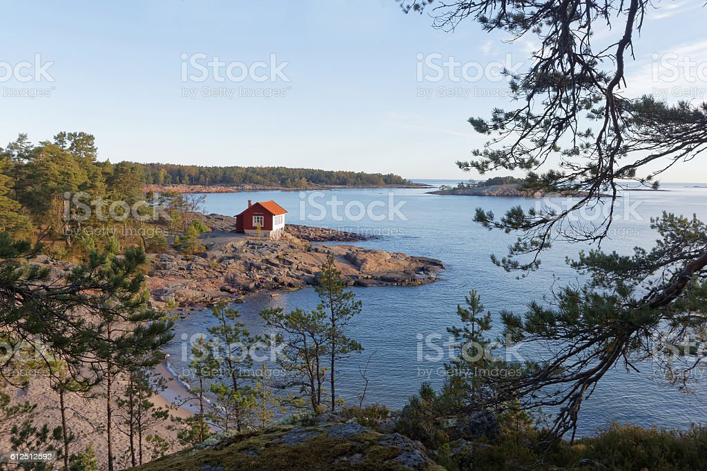 Red and white cottage on a cliff in the archilelago stock photo